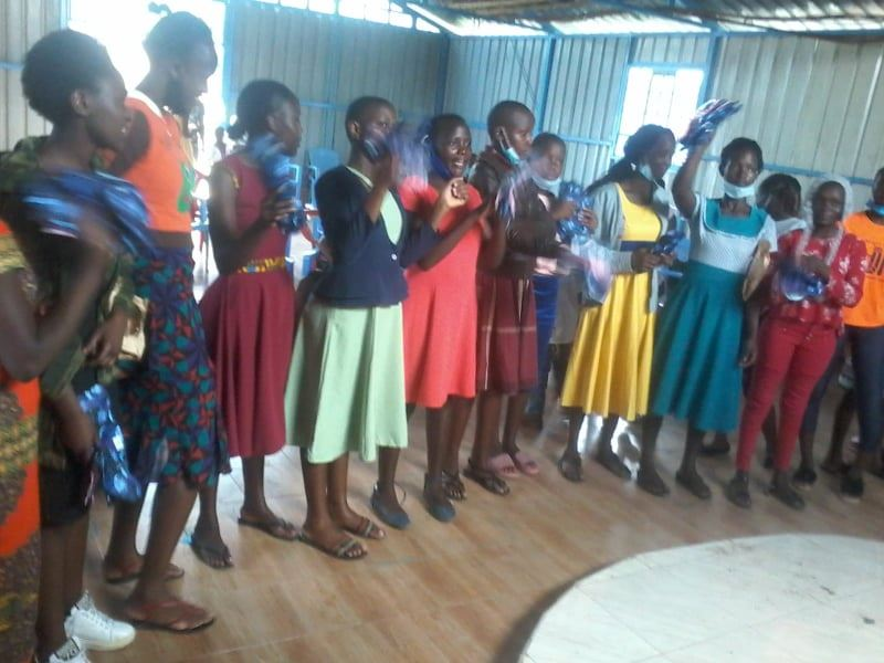 Young women who had been using old clothes and rags receiving new soft, absorbent, reusable cloth menstrual pads.
